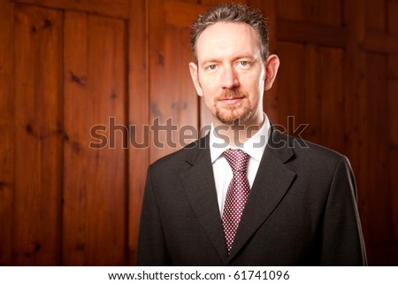 A head and shoulders businessman stood in front of some wooden panels. - stock photo