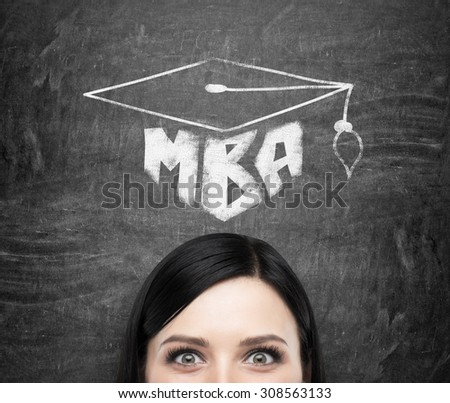 A head of young brunette lady who is thinking about MBA degree. Drawn a graduation hat on the black chalkboard background . - stock photo
