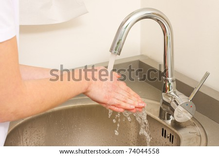 A health occupation worker washing her hands before any intervention. - stock photo