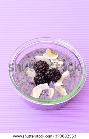 A healthy breakfast blackberries coconut chia seed pudding on purple background. Concept of healthy food. Selective focus   - stock photo