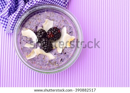 A healthy breakfast blackberry coconut chia seed pudding on purple background. Concept of healthy food. Top view. Selective focus   - stock photo