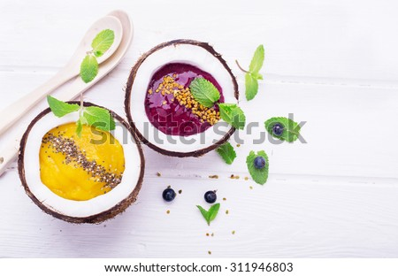 A healthy breakfast smoothie mango and berries garnished with chia seeds and bee pollen in two coconuts on a light wooden background. Concept of healthy food. Top view. selective Focus - stock photo
