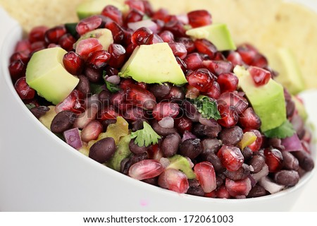 A healthy relish or salsa with pomegranate, avocado, red onions, black beans and cilantro served with corn chips.  - stock photo