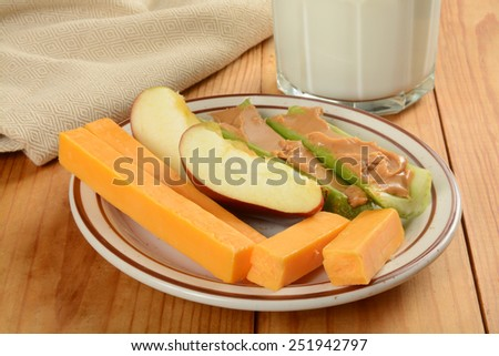 A healthy snack plate with apple slices, cheddar cheese sticks and celery stuffed with peanut butter - stock photo