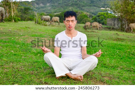 A healthy young man sitting doing yoga in outdoors - stock photo