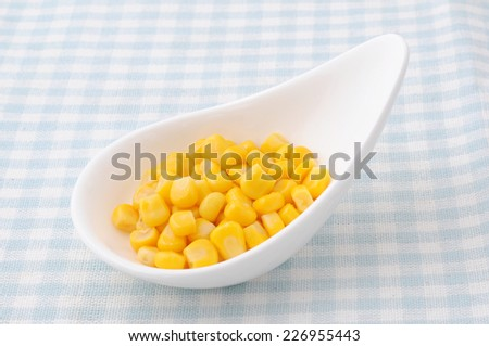 a heap of canned corn on a plate on tablecloth - stock photo