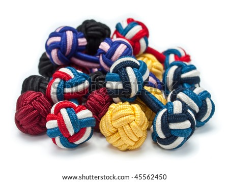A heap of differently colored silk knot style cuff links - stock photo