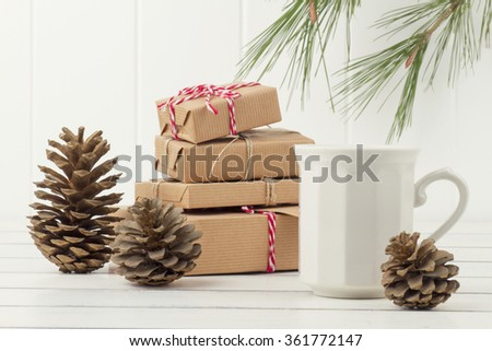 A heap of paper parcels (christmas gift boxes) wrapped with paper kraft and tied with red & white baker's twine. A cup and some pinecones. - stock photo
