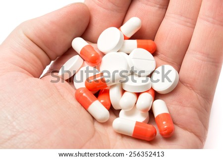 A heap of white and white-red pills lies in a hand - stock photo