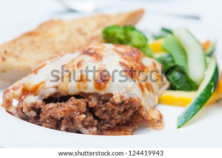 a heaping plate of lasagna dripping with melted cheese, sauteed vegetables and crisp garlic toast - stock photo