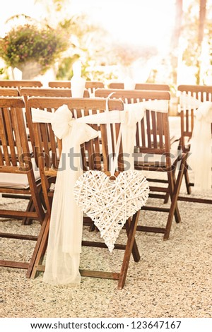 a heart hangs from a chair at a wedding - stock photo