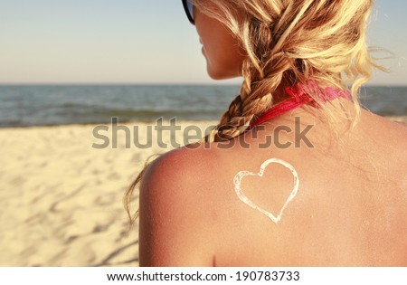a heart of the cream on the female back on the beach - stock photo