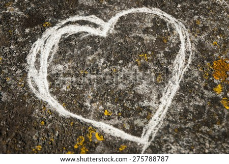 A heart shape scratched into weathered concrete. - stock photo
