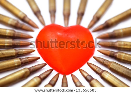 A heart shaped bar of soap is surrounded by 5.56 cartridges pointing at it. Fits the concept of 'Heart Attack'. Very shallow depth of field. - stock photo
