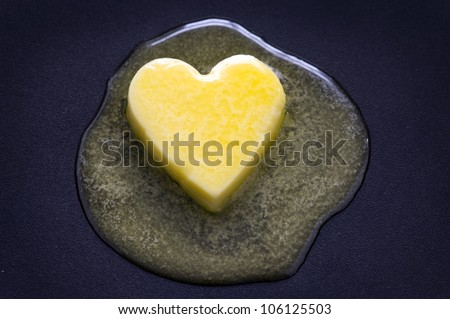a heart shaped butter pat melting on a non-stick surface - stock photo