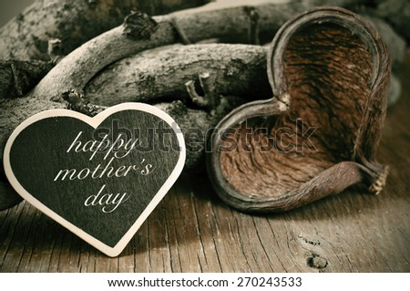a heart-shaped chalkboard with the text happy mothers day written in it and a heart-shaped fruit shell and some logs in the background, on a rustic wooden surface - stock photo