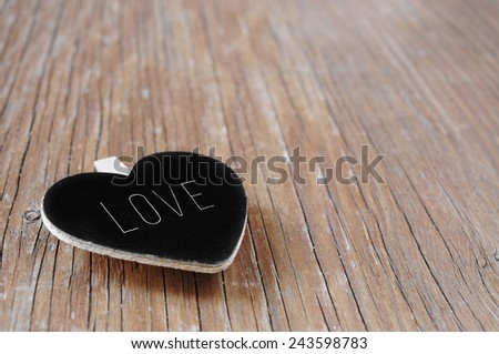 a heart-shaped chalkboard with the word love written in it on a rustic wooden surface - stock photo