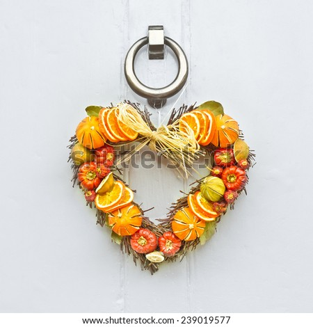 A heart shaped fruit christmas wreath on a wooden front door - stock photo