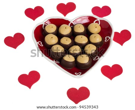 A heart shaped plate of buckeye cookies with red hearts - stock photo