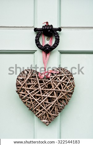A heart shaped wreath  on a front door - stock photo