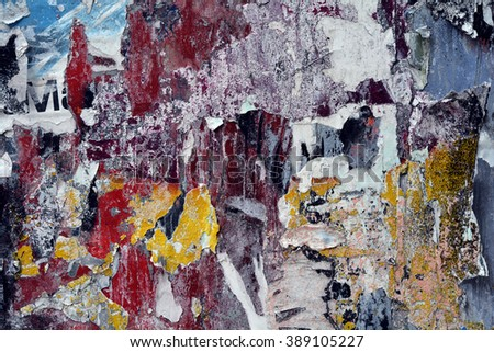 a heavily textured wall background with torn posters and paint - stock photo