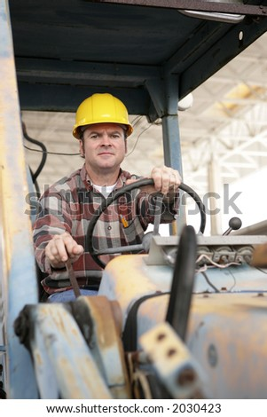 A heavy equipment operator driving a backhoe. - stock photo