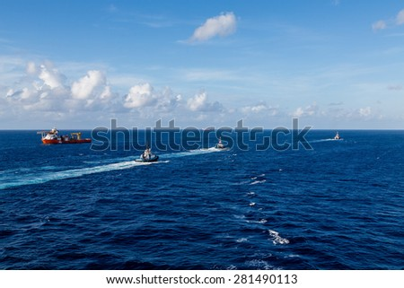 A heavy orange industrial ship on blue water accompanied by tugboats - stock photo