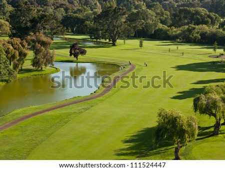 A high angle view of a golf course including a pond, cart path, and golfers. - stock photo