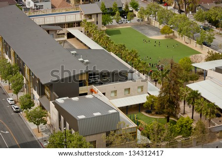 A high angle view of a new California elementary school, of modern architectural design with children playing on a grass field during recess. - stock photo