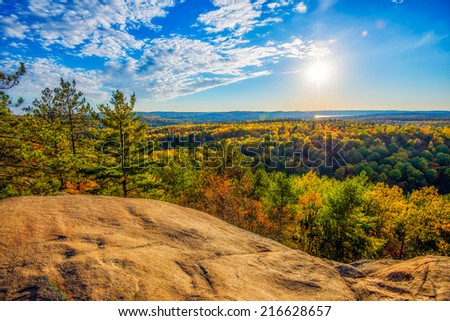 A high angle view of the colorful autumn treetops viewed from above on a rocky cliff.  Golden sunlight shines down on the landscape with soft clouds in a blue sky.  - stock photo