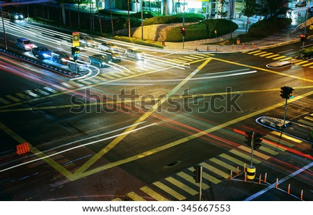 A high angle view of  treet intersection, with yellow cross walk markings, traffic signal lights, and curb cuts. - stock photo