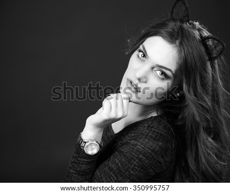 A high fashion black and white portrait of an elegant and glamorous cat woman with cool makeup and a stylish watch on the hand posing in studio. - stock photo
