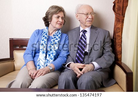 A high society senior couple (he's in his 80's, she's in her late 60's) sitting on a sofa looking away to the right side of the frame with very much love and joy. - stock photo