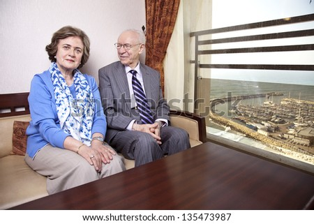 A high society senior couple (his 80's, her late 60's) sitting on a sofa. He's smiling and looking at her, and she's looking straight to the camera, with a slight smile on her face. - stock photo