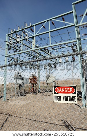 A high voltage warning sign on the fence around an electrical substation. - stock photo