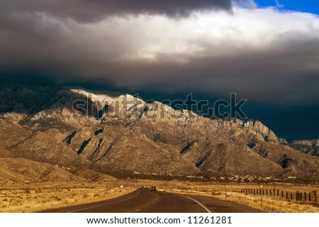 A highway in New Mexico showing the Sandia Mountains seems to lead to the awaiting thunderstorms in evening light just before sunset - stock photo