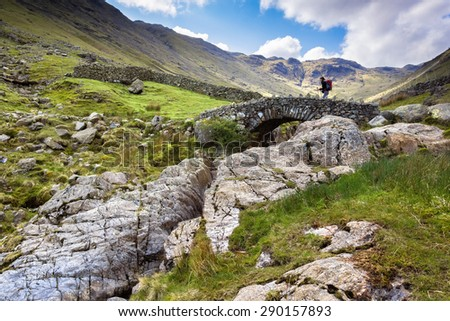 A hiker crosses Stockley Bridge from Seathwaite Fell in the Lake District, Cumbria UK. Looking up from the stream bed. - stock photo