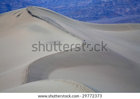 A Hiker Rests On A Mountain Of Sand, Death Valley National Park, California - stock photo