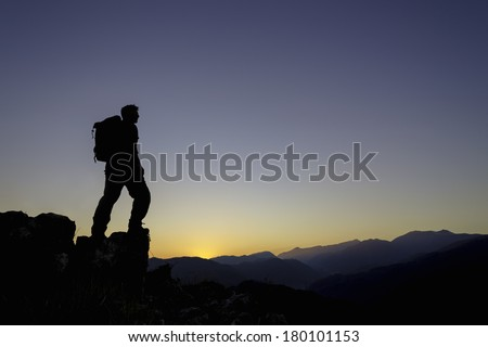 A hiker with a backpack arrives at the summit of a mountain during sunset. / Hiker at summit of mountain - stock photo