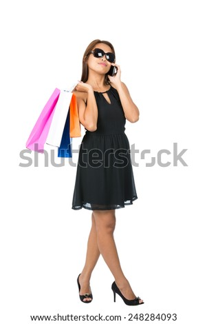A hip Asian woman casually drapes department store shopping bags over shoulder wearing stylish black dress, sunglasses, head tilted talking on cell phone looking away. Thai national of Chinese origin - stock photo