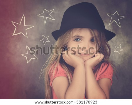 A hipster child with a black hat is happy with stars drawn out on a chalkboard wall for a fashion or style concept. - stock photo