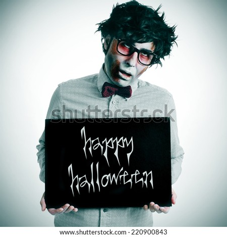 a hipster zombie showing a black signboard with the text happy halloween written in it - stock photo