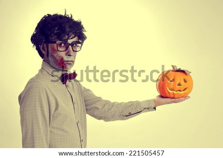 a hipster zombie with a jack-o-lantern in his hand, like Hamlet, with a retro effect - stock photo
