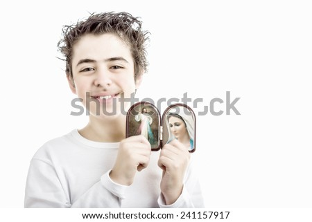 A hispanic boy holds Icons in a wooden rounded case of Merciful Jesus and Our Lady of Medjugorje, the Blessed Virgin Mary - stock photo