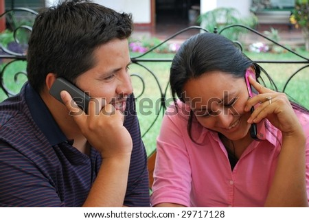 A Hispanic couple.  Both are talking on the phone. - stock photo