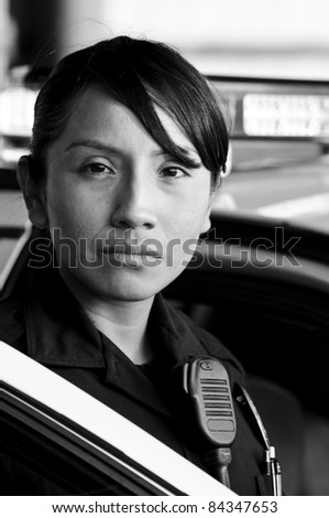 a Hispanic female police officer looking serious while standing at her patrol car. - stock photo