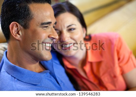 A hispanic man and a caucasian woman sit together close on a yellow couch, she looking up at him admiringly. - stock photo