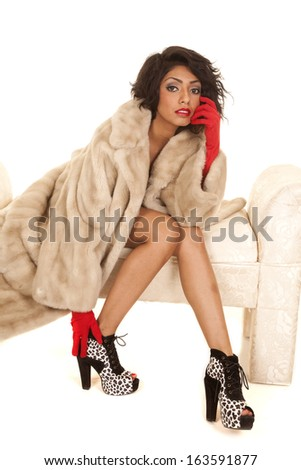 A Hispanic woman sitting on a bench in her fur coat and red gloves. - stock photo