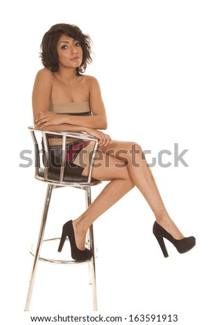 a Hispanic woman sitting on her stool in her short dress. - stock photo