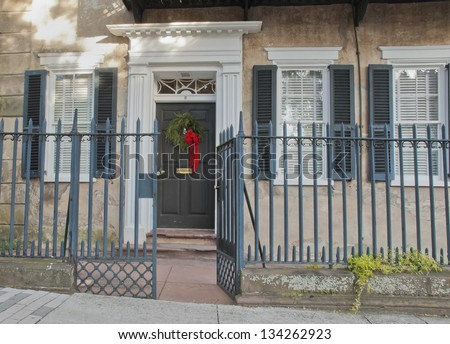A historic home's doorway in Charleston is decorated with a Christmas Wreath. - stock photo